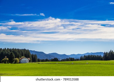 Beautiful mountains landscape with house, green meadow, forest and blue sky