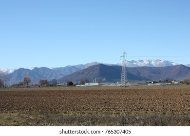 A beautiful mountains with a lot of snow in winter time are behind the farm in Europe. It is such a wonderful view and landscape.