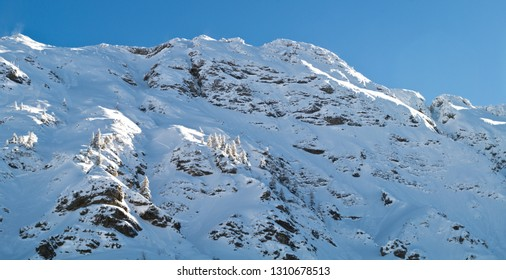 A beautiful mountainside covered with snow on a sunny day