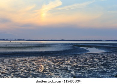 beautiful mudflat with low tide through salt marsh along the sea with sunset at a hot summer evening