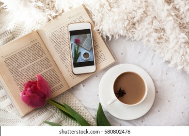 beautiful mug with hot coffee, reading a book in the morning, spring tulip