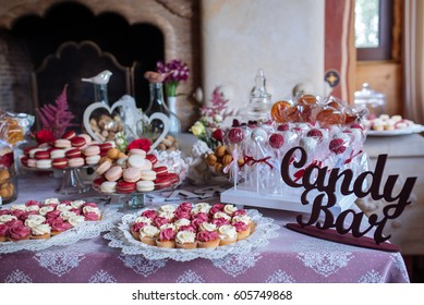 Beautiful multi colored decorated baked sweet tasty candy bar dessert party with happy people around, catering banquet table. macaroons
