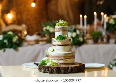 Beautiful multi level naked wedding cake, decorated with cream and fresh flowers, greenery. Delicious dessert at wedding banquet standing on wooden plate
