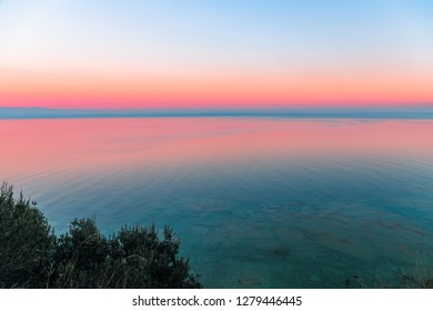 Beautiful multicolor sunset reflected in the waters of Lake Garda, Italy. Skyline. Visible coastline in the evening fog. Winter time. View from the Sirmione peninsula, Italy.
