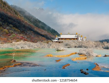 Beautiful Multi-Colored Pond (Huanglong Middle Temple on background) in the Huanglong National Park near Jiuzhaijou after snowfall - SiChuan, China