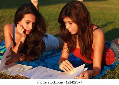 Beautiful multicultural young college women studying outdoors on campus.