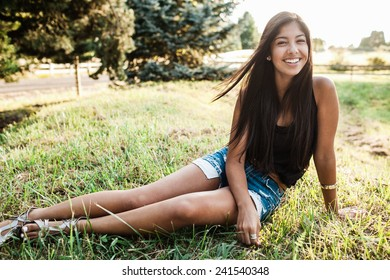 Beautiful multicultural young woman outdoor portrait on farm on grass with sunset behind
