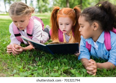 beautiful multiethnic schoolgirls reading book while lying together on grass