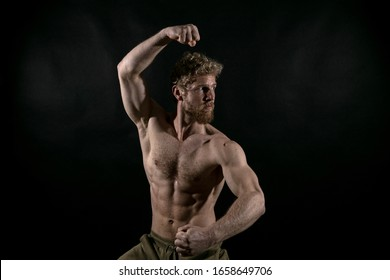 Beautiful muscles, athletic body. Studio photography on a black background, naughty light. Combat sport. Fair-haired sports man