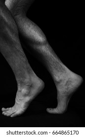 Beautiful, muscular, bare male feet on a black background. Classic high-contrast art photo