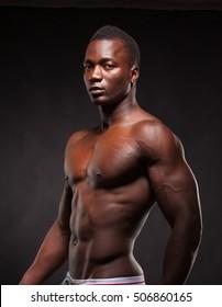 Beautiful and muscular black man on dark background