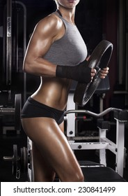 beautiful muscular fit woman exercising in a gym