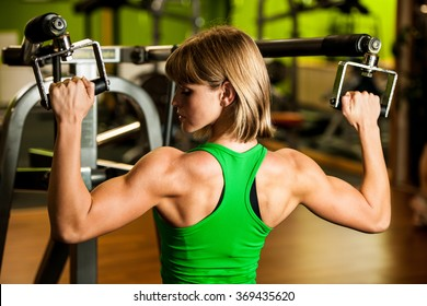 beautiful muscular fit woman exercising building muscles in fitness gym