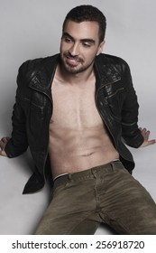 Beautiful muscular male model with nice abs in leather jacket