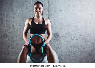 Beautiful muscular woman doing exercise withspring hoop on a gray background. Pilates Ring.Concrete wall in the background