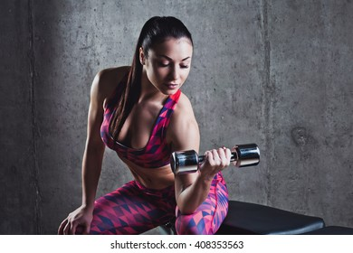 Beautiful muscular woman doing exercise with dumbbells on a gray background..Concrete wall in the background