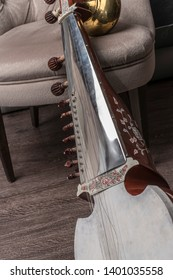 Beautiful musical object. Beautiful view of the antique Indian national stringed plucked musical instrument, guitar-like sitar, in the interior, against a dark background.