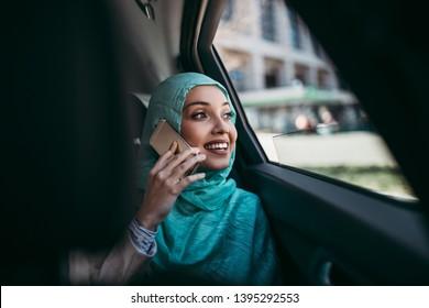 Beautiful muslim arabian woman with hijab sitting on backseat in luxury car. She using her smart phone and looking through window.