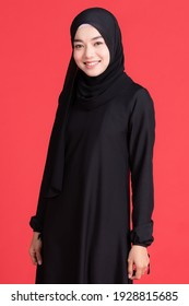 Beautiful Muslim Asian woman wearing black hijab, standing pose and smiling cheerful on red background. In religious rituals  concept.