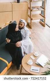 beautiful muslim couple embracing on couch in modern cafe