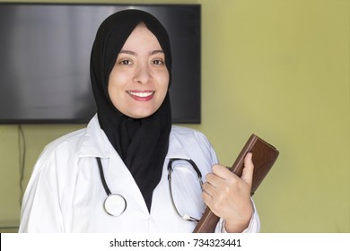 beautiful muslim doctor algerian woman with a beautiful smile hold o brown notebook