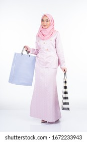 A beautiful Muslim female model in a Asian traditional dress carrying shopping bags isolated on white background. Idul fitri festive preparation shopping concept. Full length portrait.