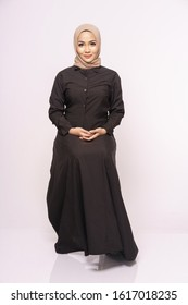 Beautiful Muslim female models wearing black long sleeves dress with hijab sitting on a chair, isolated over white background. Stylish Muslim female hijab fashion lifestyle portraiture concept.