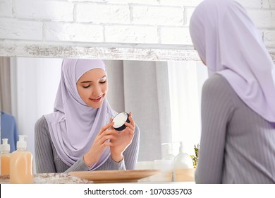 Beautiful Muslim girl with acne problem using cream while looking in mirror indoors