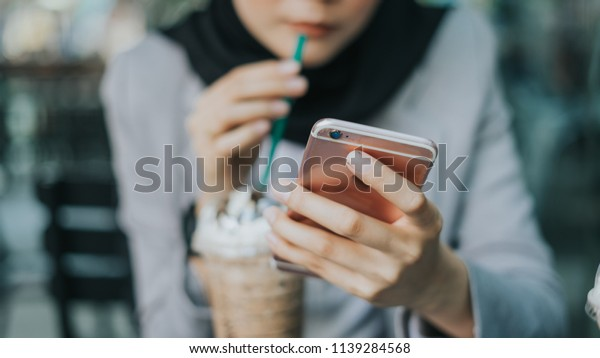 Beautiful Muslim girl with hijab using smartphone while drinking at cafeteria.Business woman using phone.