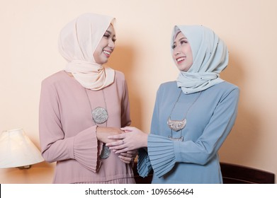 Beautiful Muslim girls shaking hand during Aidilfitri celebrations.Girls wearing hijab with smile face during eid ul fitr festival. Aidilfitri scenery.