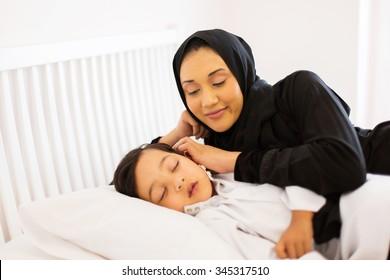 beautiful muslim mother watching her son sleeping in bed