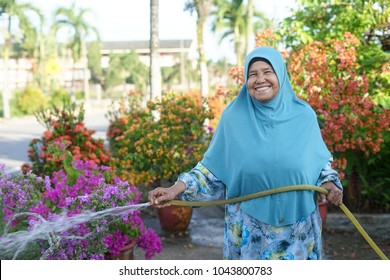 Beautiful Muslim mother/woman /malaysian/asian/Indonesian/ watering the flower at the garden