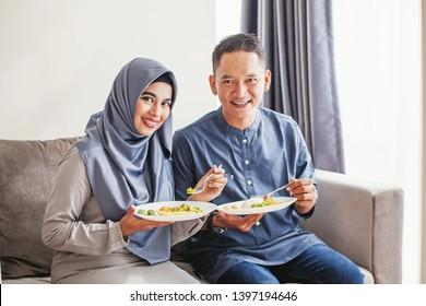 Beautiful muslim southeast asian couple eating nasi campur together, looking at camera