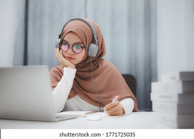 Beautiful muslim student girl using a laptop computer learning online at home. Distance learning online education.