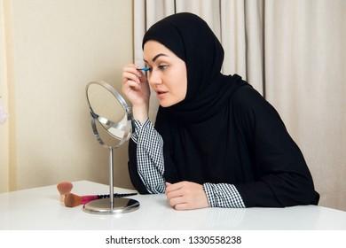 Beautiful muslim woman applying mascara. Young arab woman using lash brush