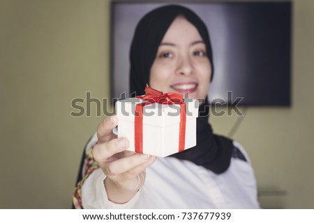 beautiful muslim woman with cheerful smile give you white gift box with red ribbon
