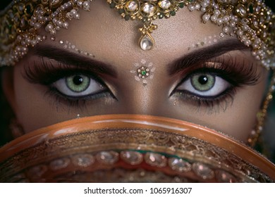 Beautiful Muslim Woman face portrait with bindis and paint.  Close up of beauty arabian or indian woman with perfect makeup and big green eyes.