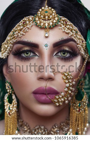 Beautiful Muslim Woman face portrait with bindis and paint. Close up of beauty indian woman with perfect makeup and big green eyes.