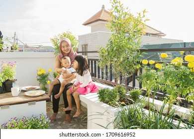 beautiful muslim woman having breakfast with children at her rooftop garden together