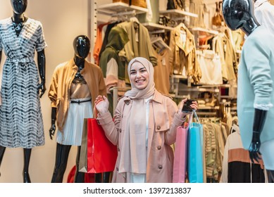 Beautiful Muslim woman in headscarf and fashionable modern clothes holds shopping bags and smart phone.Modern Muslim women lifestyle or travel tourist concept