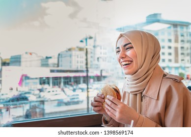 Beautiful Muslim woman in headscarf and fashionable modern trendy clothes eats big hamburger in restaurant with happy smiling.Modern Muslim woman lifestyle or business  concept