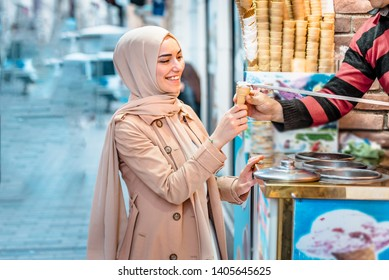Beautiful Muslim woman in headscarf and fashionable modern clothes laughes because of Ice cream seller man playing traditional Turkish joke.Modern Muslim women lifestyle or travel tourist concept