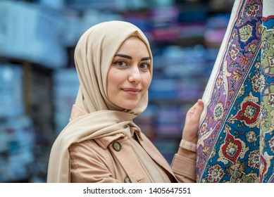 Beautiful Muslim woman in headscarf and fashionable modern clothes looks atrug or carpet sold in Egypt Bazaar,Istanbul,Turkey.Modern Muslim women lifestyle travel tourist concept