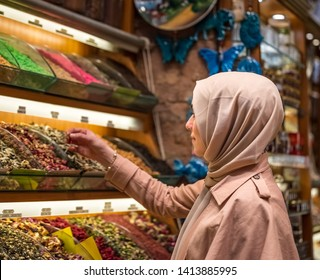 Beautiful Muslim woman in headscarf and fashionable modern clothes looks spices and dried herbal tea flowers in Egypt Bazaar,Istanbul,Turkey.Modern Muslim women lifestyle travel tourist concept