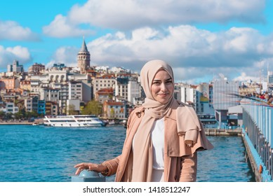 Beautiful Muslim woman in headscarf and fashionable modern trendy clothes stands with view of Galata Tower and Bridge in Istanbul,Turkey.Modern Muslim woman lifestyle or travel tourist concept
