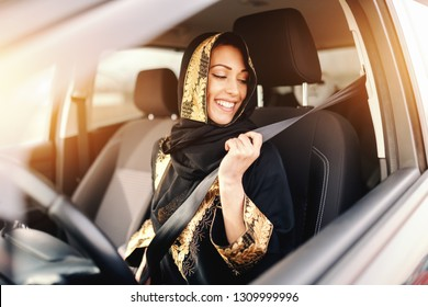 Beautiful muslim woman preparing for driving, setting up seat belt.
