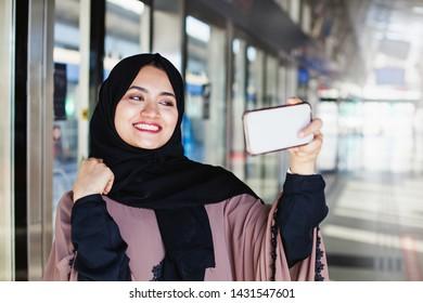 Beautiful muslim woman taking selfie on metro station, Dubai