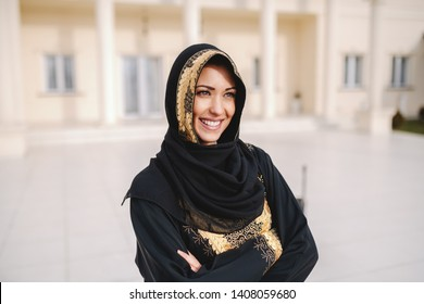 Beautiful Muslim woman in traditional wear standing in front of her house with arms crossed.