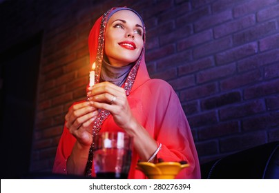 Beautiful muslim woman waiting for an evening time to take Iftar - evening meals of Ramadan month