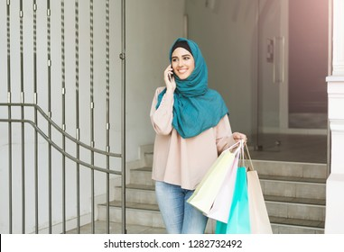 Beautiful muslim woman wearing hijab going out from boutique with many shopping bags, talking by phone. Plesant shopping day concept